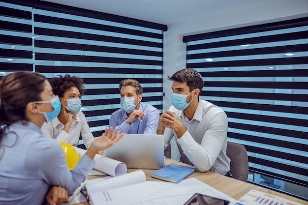 회의실에 앉아 얼굴에 마스크를 쓴 건축가의 다민족 그룹, 회의를 갖고 코로나 발생 중 프로젝트에 대해 논의