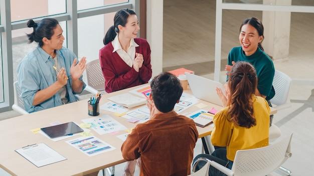 Многорасовая группа молодых творческих людей из азии в элегантной повседневной одежде обсуждает бизнес, хлопая в ладоши, смеясь и улыбаются вместе на собрании мозгового штурма в офисе. успешная концепция совместной работы коллег.