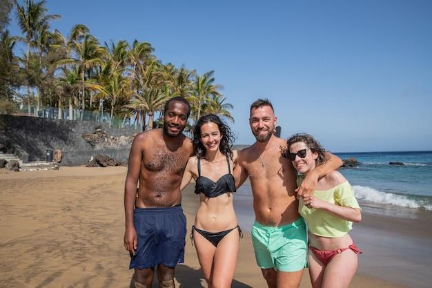 多民族の友人グループがビーチで楽しみ、休日を楽しんでいます。