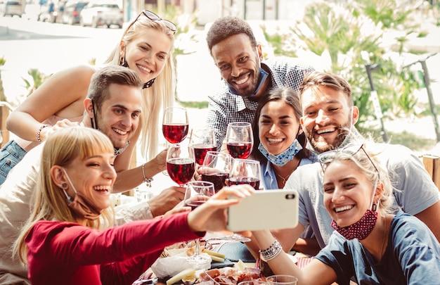 レストランで防護マスクを着ている友人の多民族のグループ。スマートフォンでselfieを取って赤ワインを乾杯を祝う幸せな人々。
