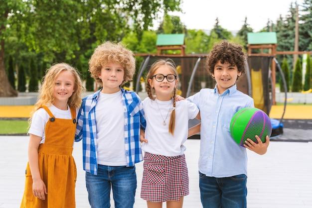休憩中に遊び場で遊ぶ子供たちの多民族グループ-楽しんでいる遊び心のある小学生