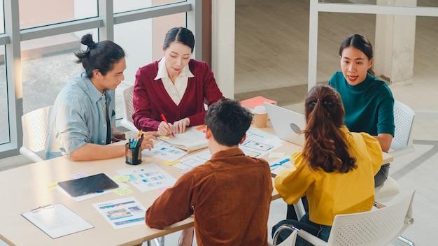 現代のオフィスでビジネスブレーンストーミング会議アイデアモバイルアプリケーションソフトウェア設計プロジェクトを議論するスマートカジュアルな服装の若い創造的な人々の多民族グループ。同僚のチームワークの概念。