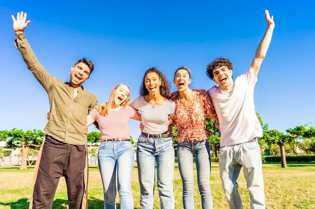 都市公園の自然の中でお互いを抱きしめているカメラを見ながら、腕を上げてポーズをとっている若い友人の多民族グループ。人生と成功を楽しんで一緒に楽しんでいる幸せな多様な人々