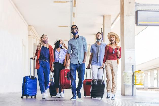 休暇中に駅を歩いているフェイスマスクを身に着けている若者の多民族グループ。新しい通常の旅行と休日の概念。