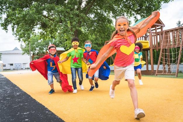 スーパーヒーローの衣装を着て、屋外で楽しんでいる若い学生の多民族グループ
