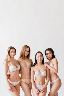 Multiracial group of positive women posing in lingerie