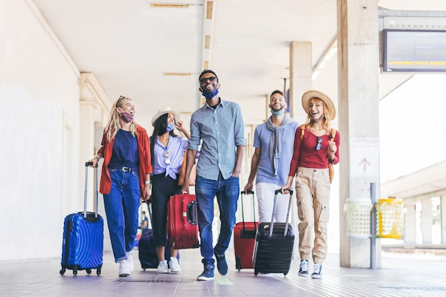 Multiracial group of young people wearing face mask walking at train station at vacation. new normal travel and holiday concept.
