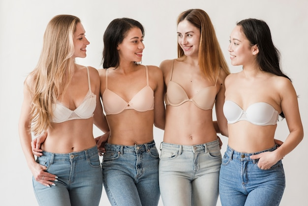 Multiracial group of young women wearing bras embracing and smiling