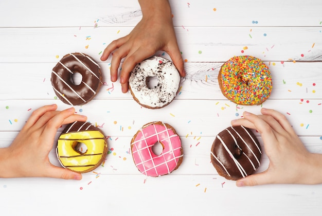 Multiracial hands are with taking colorful donuts.