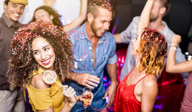 Multiracial happy friends having fun drinking wine at eve celebration party