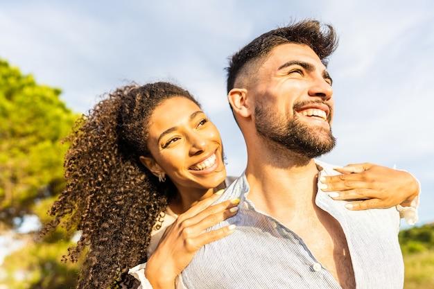夕日にキスされた地平線を見て夕暮れ時に自然の中で屋外で楽しんでいる愛の多民族の幸せな若い美しいカップル。彼女のボーイフレンドを後ろから抱きしめる歯を見せる笑顔のアフリカ系アメリカ人の女の子