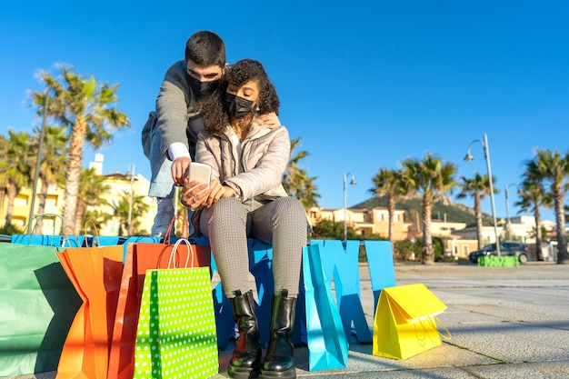 Многорасовая гетеросексуальная пара молодых людей на открытом воздухе, сидящих на скамейке среди разноцветных сумок для покупок, использует и указывает на телефон, чтобы делать покупки в интернете, в защитной маске от коронавируса.