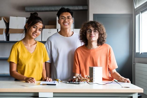 カメラを見ている電子工学のクラスの多民族の高校生。教育の概念。協力の概念。