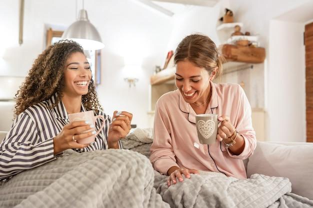 Многорасовая гомосексуальная женская пара веселится дома, сидя на диване, попивая чашку чая под одеялом - две красивые молодые женщины связывают друг друга