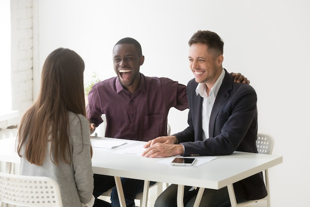 Multiracial hr managers laughing at funny joke interviewing woman applicant