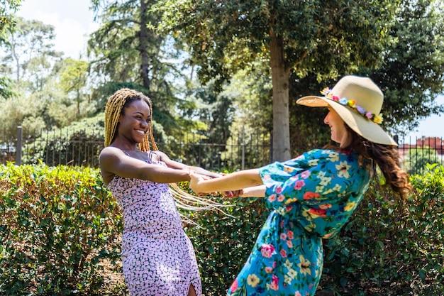 Многорасовая лесбийская пара держится за руки и кружится, стоя вместе в парке лгбт
