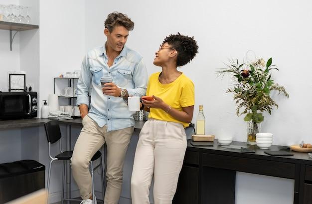 Многорасовые мужчина и женщина в коворкинге за чашкой кофе