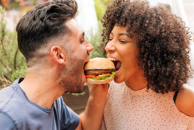 Multiracial man and woman eating tasty hamburger together during romantic date in restaurant in summer