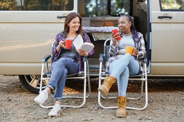 キャンピングカーとのロードトリップで自然の中でリラックスする多民族の成熟した女性-コーヒーを飲みながら、スマートフォンを使用して本を読んでいる間、ミニバンの前の森に座っている先輩の友人