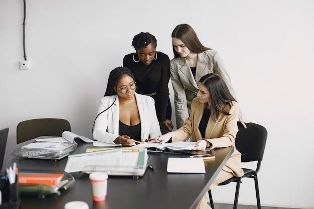 Девушки многорасовых офисных работников работают вместе, сидя за столом. обсуждение бизнес-проекта