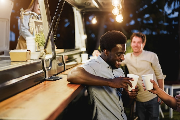 Multiracial people cheering with drinks in counter at food truck restaurant outdoor - focus on african american man face