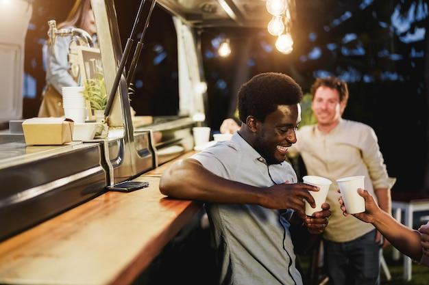야외 푸드 트럭 레스토랑 카운터에서 음료를 마시며 환호하는 다인종 사람들 - 아프리카계 미국인 남자 얼굴에 초점