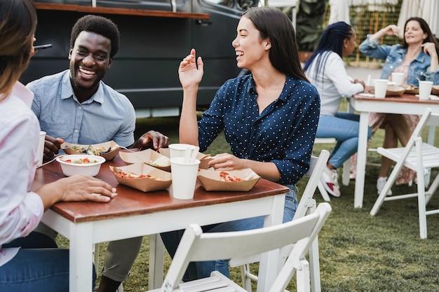 야외 푸드 트럭 레스토랑에서 식사하는 다인종 사람들 - 아프리카 남자 얼굴에 초점