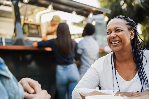 Многорасовые люди едят в ресторане-фургоне на открытом воздухе - внимание на лицо африканской женщины
