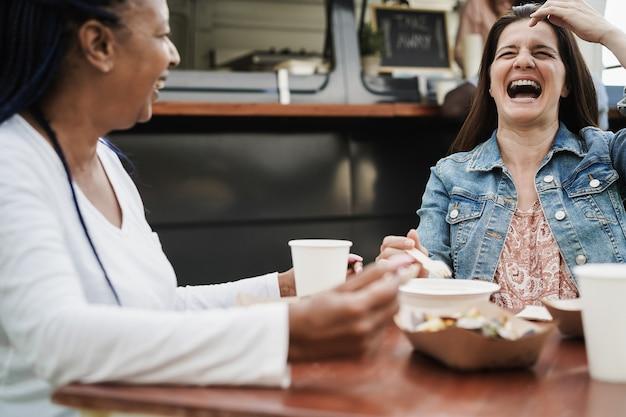屋外のフードトラックレストランで食べる多民族の人々-ヒスパニック系の女性の顔に焦点を当てる