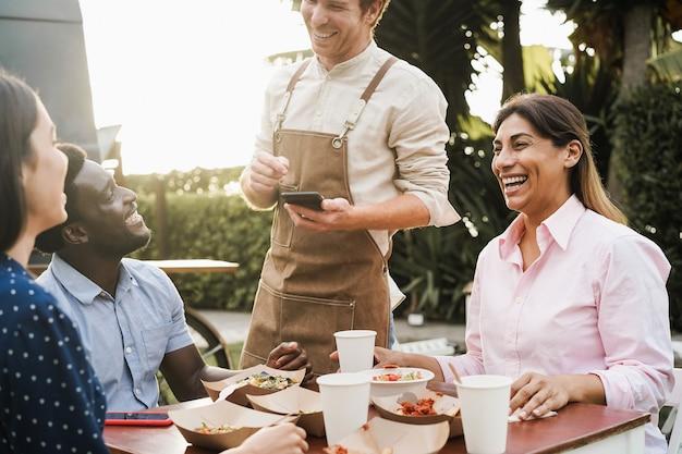Многорасовые люди едят в ресторане на открытом воздухе - фокус на лице зрелой женщины