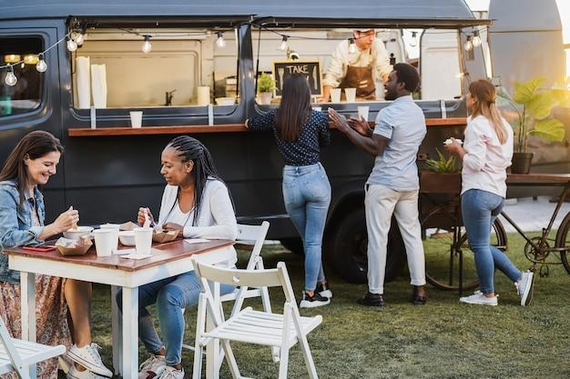 야외 음식 트럭 미식가 음식을 먹는 다민족 사람들-건강한 식사와 저녁 식사 개념-아프리카 여자 얼굴에 초점