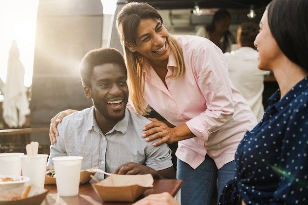 Multiracial people eating at food truck restaurant outdoor - focus on center woman face