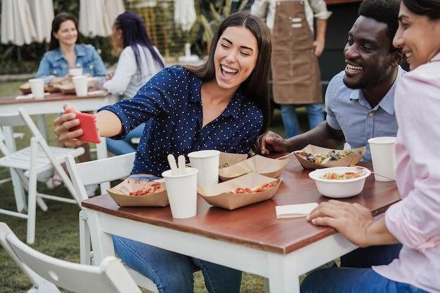 야외 푸드트럭 레스토랑에서 휴대폰으로 셀카를 찍는 다인종 사람들 - 아프리카계 미국인 남성의 얼굴에 초점