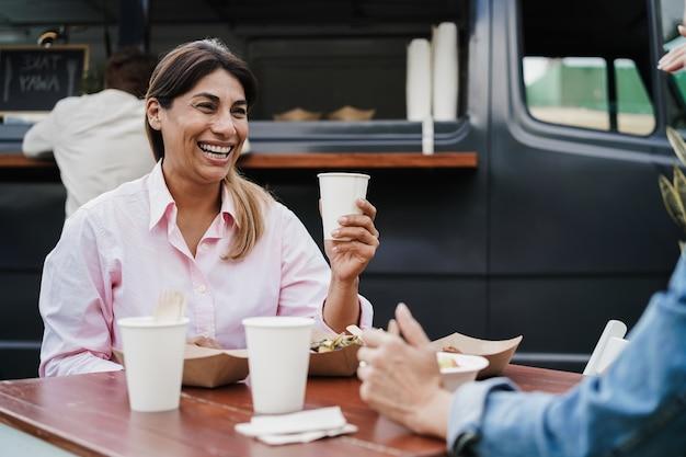 푸드 트럭 레스토랑에서 야외에서 먹고 마시는 것을 즐기는 다인종 사람들 - 여성의 얼굴에 초점