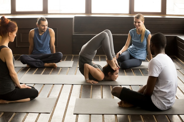 Multiracial people looking at instructor performing yoga pose at