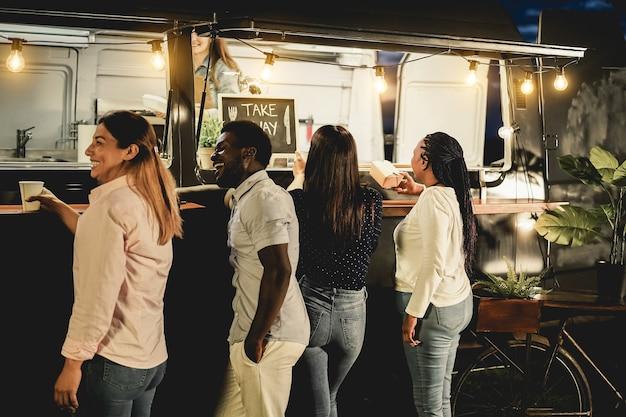 테이크 아웃 푸드 트럭 카운터에서 음식을 주문하는 다인종 사람들 - 오른쪽 아프리카 여성에 초점