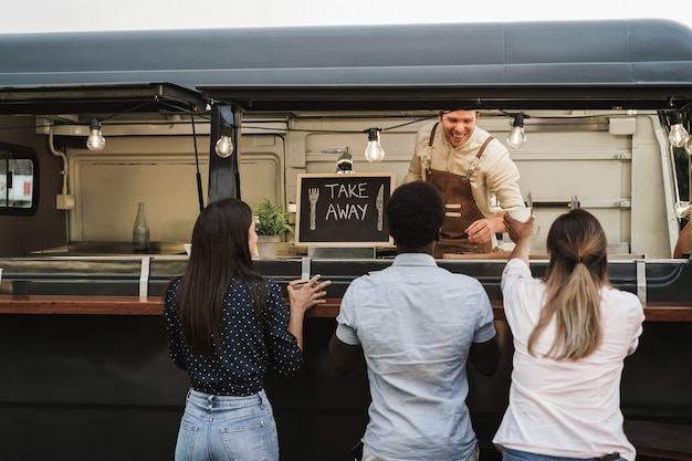 Multiracial people ordering food at counter in food truck outdoor - focus on take away sign