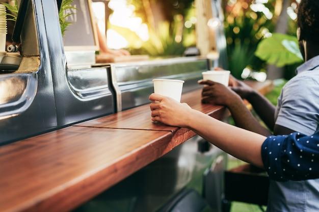 야외 음식 트럭 앞에서 미식가 음식을 주문하는 다민족 사람들-여름과 저녁 식사 개념-백인 여자 손에 초점