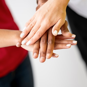 Multiracial people putting their hands together