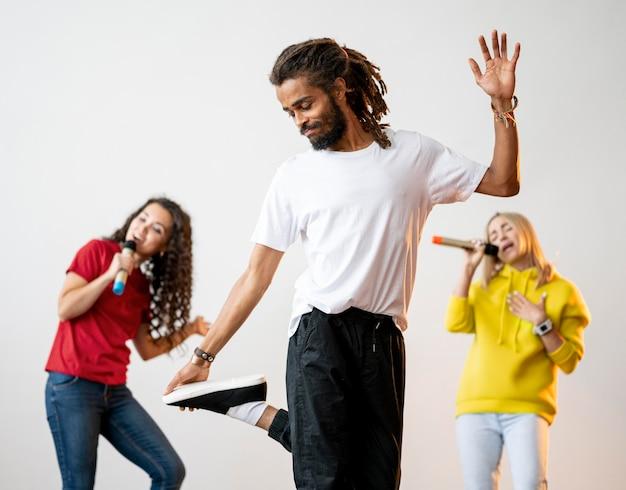 Многорасовые люди поют и танцуют вместе