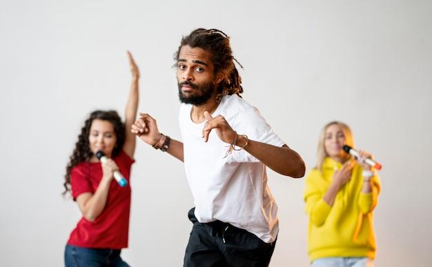 Многорасовые люди поют и танцуют