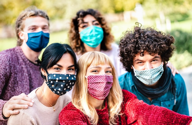 Multiracial people taking selfie wearing face mask and spring clothes