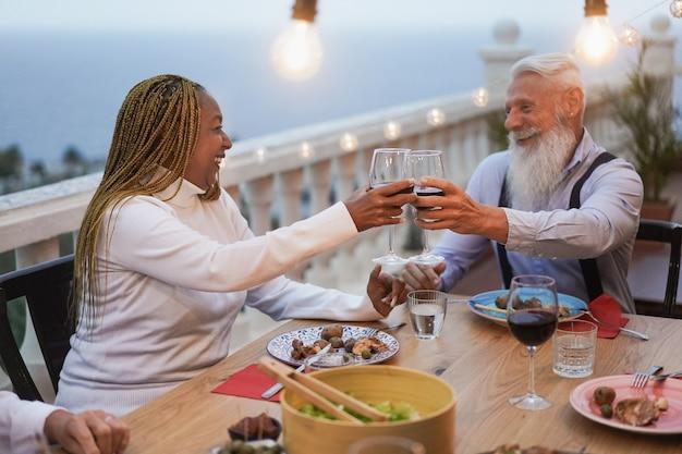 Многонациональные старшие друзья ликуют с вином во внутреннем дворике - пожилые люди вместе празднуют во время ужина на террасе ресторана
