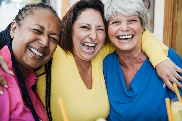 Многонациональные старшие друзья веселятся на открытом воздухе в баре-ресторане - сосредоточьтесь на лице старшего в центре