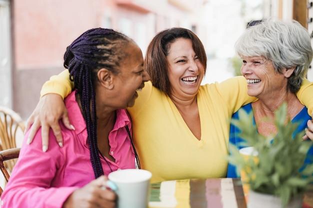 多民族の先輩の友人がバーのレストランで一緒にコーヒーを飲みながら屋外のバーで会ってチャットする-中央の女性の顔に焦点を当てる