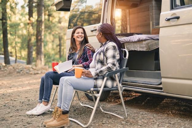 多民族の年配の女性は自然の中でミニバンキャンピングカーの休暇を楽しんでいます-友情と休日のコンセプト