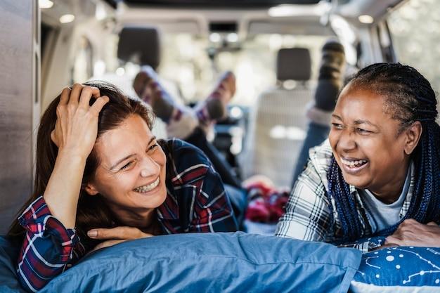 Многонациональные пожилые женщины-подруги развлекаются в кемпинге в автофургоне - сосредоточьтесь на правом африканском женском глазу
