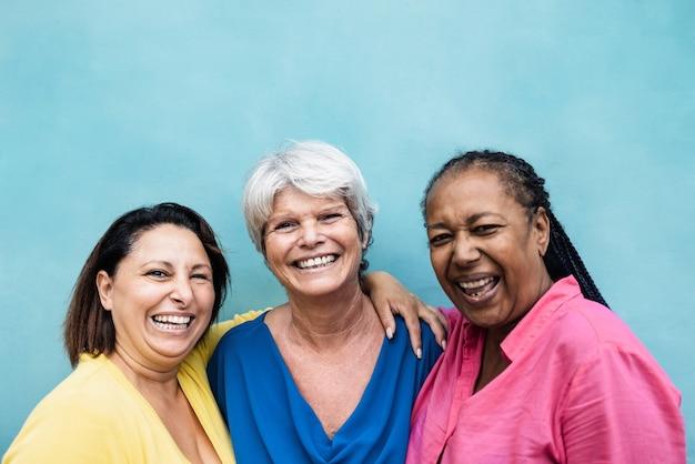 屋外で一緒に抱き締めることを楽しんでいる多民族の年配の女性-中央の女性の顔に焦点を当てる