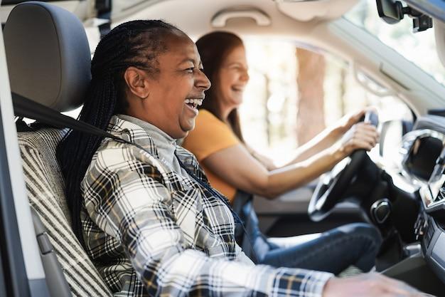 Многонациональные пожилые женщины веселятся на дороге в автофургоне - фокус на лице африканской женщины
