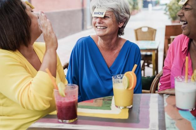 バーレストランで額の推測ゲームを楽しんでいる多民族の年配の女性-中央の女性の顔に焦点を当てる